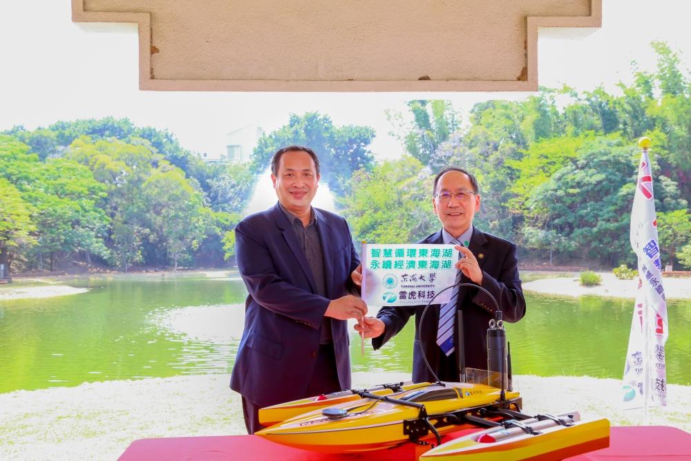 東海大學校長王茂駿(右)與雷虎科技股份有限公司董事長陳冠如交換旗幟,見證巡航小艇